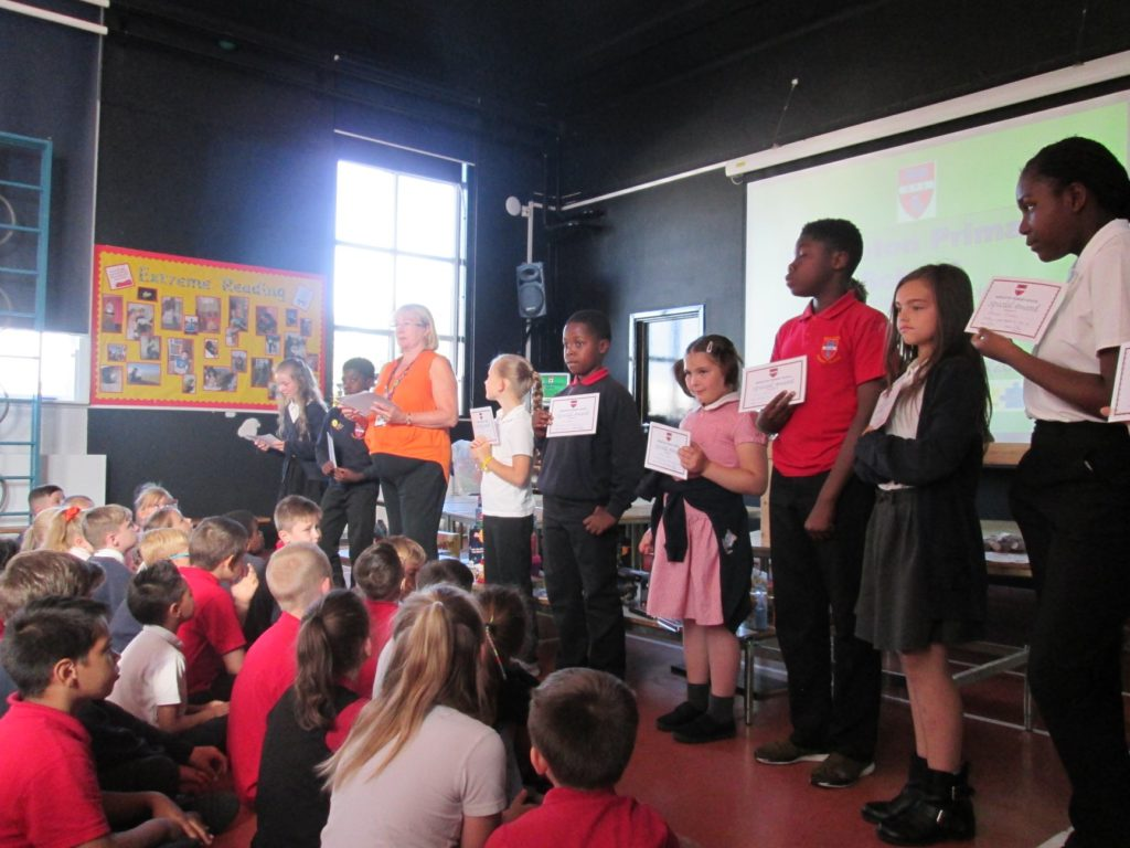 pupils on stage receiving certificates